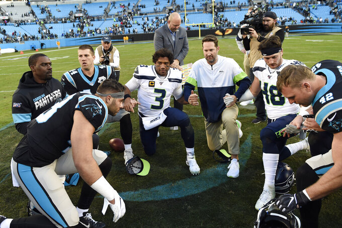 Seattle Seahawks quarterback Russell Wilson (3) along with other Seahawks and Carolina Panthers players huddle following an NFL football game in Charlotte, N.C., Sunday, Dec. 15, 2019. (AP Photo/Mike McCarn)