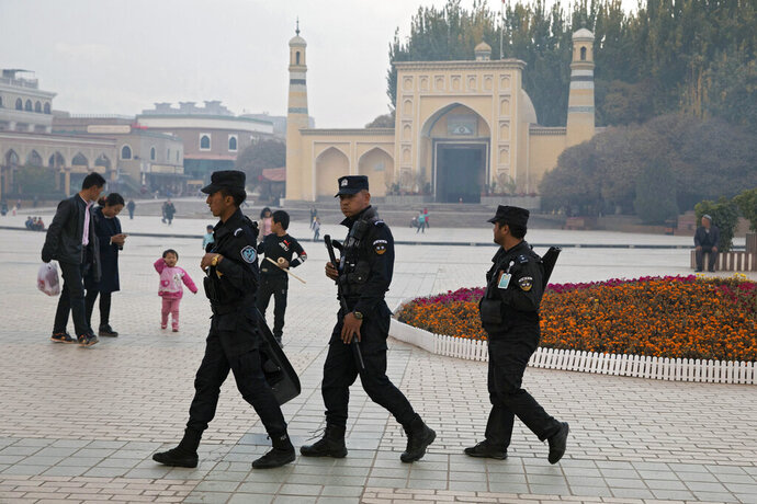 FILE - In this Nov. 4, 2017, file photo, Uighur security personnel patrol near the Id Kah Mosque in Kashgar in western China's Xinjiang region. China on Wednesday, Dec. 4, 2019, has responded with swift condemnation after U.S. Congress overwhelmingly approved a bill targeting its mass crackdown on ethnic Muslim minorities. (AP Photo/Ng Han Guan, File)