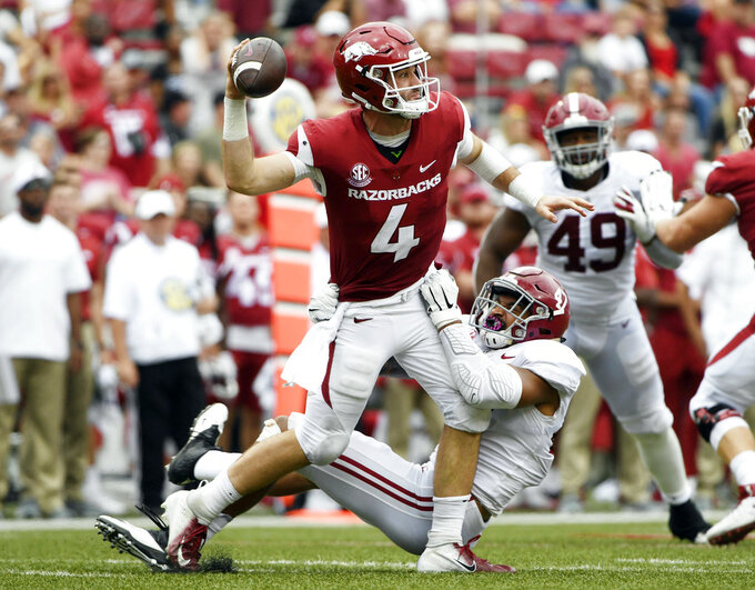 Alabama defender Christian Miller puts the pressure on Arkansas quarterback Ty Storey, top, as he throws a pass in the first half of an NCAA college football game Saturday, Oct. 6, 2018, in Fayetteville, Ark. (AP Photo/Michael Woods)