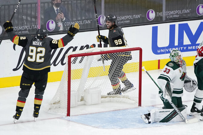 Vegas Golden Knights left wing Tomas Nosek (92) and right wing Alex Tuch (89) celebrate after defenseman Brayden McNabb (3), not pictured, scored against the Minnesota Wild during the third period of an NHL hockey game Thursday, April 1, 2021, in Las Vegas. (AP Photo/John Locher)