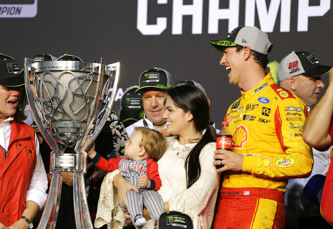 Joey Logano, right, stands with his wife Brittany Baca, and their son Hudson after winning the NASCAR Cup Series Championship auto race at the Homestead-Miami Speedway, Sunday, Nov. 18, 2018, in Homestead, Fla. (AP Photo/Terry Renna)