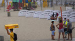 A vendor, left, carries a box selling Boules de Berlin at the Belgian seaside resort of Blankenberge, Belgium, Tuesday, Aug. 11, 2020.  A skirmish took place on the beach on Saturday, Aug. 8, 2020 which resulted in two coastal communities banning day trippers from the city. (AP Photo/Virginia Mayo)
