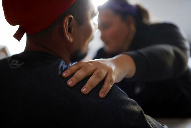 In this Dec. 14, 2019, photo, Dr. Psyche Calderon works with a patient in a shelter for migrants in Tijuana, Mexico. Calderon is a general practitioner volunteering her time to provide care for Central Americans stuck in Mexico while they try to obtain asylum in the United States. (AP Photo/Gregory Bull)