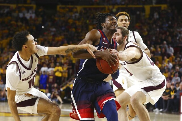 Arizona guard Dylan Smith, middle, gets fouled as he gets past Arizona State guard Jaelen House (10), Arizona State forward Mickey Mitchell, right, as Arizona State forward Jalen Graham, back right, looks on during the first half of an NCAA college basketball game Saturday, Jan. 25, 2020, in Tempe, Ariz. (AP Photo/Ross D. Franklin)