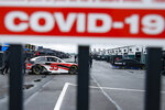 Crew members are visible under a COVID-19 alert sign as they push the car of Christopher Bell through the garage area in the morning before a scheduled NASCAR Cup Series auto race at Pocono Raceway, Saturday, June 27, 2020, in Long Pond, Pa. (AP Photo/Matt Slocum)