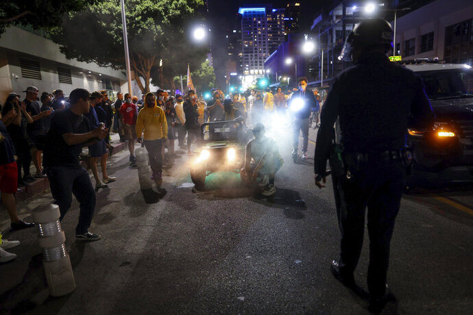 A Los Angeles Police officer attempts to disperse rowdy fans outside of Staples Center, Sunday, Oct. 11, 2020, in Los Angeles, after the Lakers defeated the Miami Heat in Game 6 of basketball's NBA Finals to win the championship. (AP Photo/Christian Monterrosa)