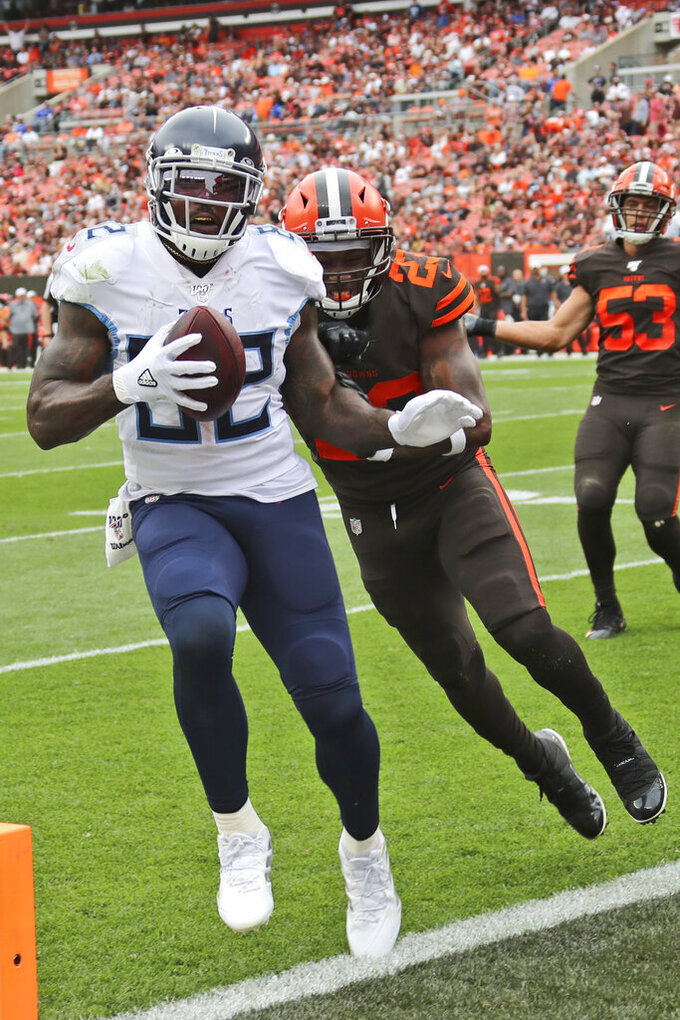 Tennessee Titans tight end Delanie Walker (82) scores a touchdown ahead of Cleveland Browns strong safety Damarious Randall (23) during the second half in an NFL football game Sunday, Sept. 8, 2019, in Cleveland. (AP Photo/Ron Schwane)