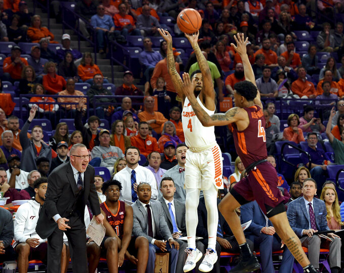 Clemson's Shelton Mitchell (4) shoots a 3-pointer over Virginia Tech's Nickeil Alexander-Walker during the first half of an NCAA college basketball game Saturday, Feb. 9, 2019, in Clemson, S.C.. (AP Photo/Richard Shiro)