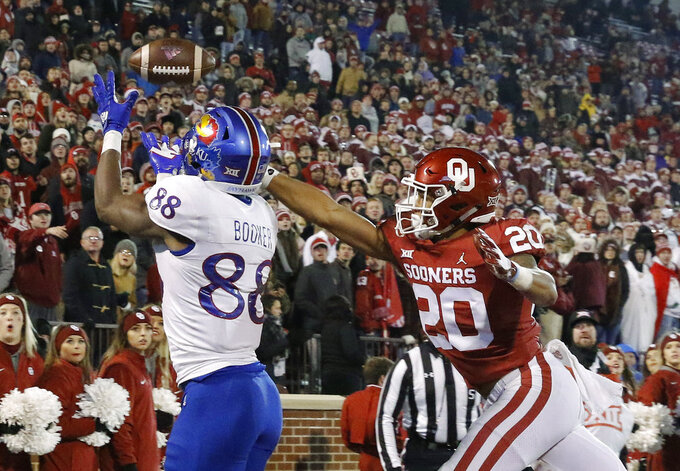 Kansas wide receiver Jeremiah Booker (88) makes a catch for a touchdown ahead of Oklahoma safety Robert Barnes (20) during the second half of an NCAA college football game in Norman, Okla., Saturday, Nov. 17, 2018. Oklahoma won 55-40. (AP Photo/Alonzo Adams)