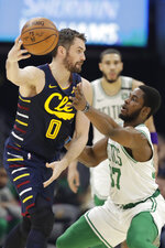 Cleveland Cavaliers' Kevin Love (0) passes against Boston Celtics' Semi Ojeleye (37) in the first half of an NBA basketball game, Wednesday, March 4, 2020, in Cleveland. (AP Photo/Tony Dejak)