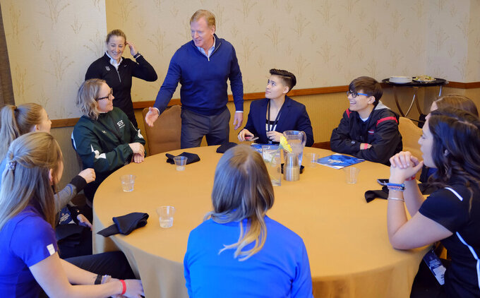 FILE - In this Feb. 26, 2019, file photo, NFL Commissioner Roger Goodell greets Saskatchewan equipment manager/team administrator Andrea Eccleston and other participants, including Bear Lake High School offensive coordinator Sam Mullet, right wearing glasses, at the NFL Women's Forum held in Indianapolis. According to 2019 research by the Institute for Diversity and Ethics in Sport, there are 73 female vice presidents throughout the league. The NFL's COO is Maryann Turcke. One-third of the working force in NFL offices is made up of women. (AP Photo/AJ Mast, File)