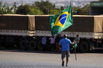A truck driver carries a Brazilian flag as truckers gather at a gas station to show support for Brazilian President Jair Bolsonaro, just south of Brasilia, Brazil, Thursday, Sept. 9, 2021. Bolsonaro rallied supporters two days prior to coincide with Independence Day but truckers remain mobilized. (AP Photo/Eraldo Peres)