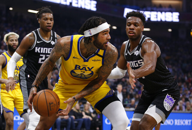 Golden State Warriors center Willie Cauley-Stein, front left, looks to pass against Sacramento Kings guard Buddy Hield, right, during the first quarter of an NBA basketball game in Sacramento, Calif., Monday, Jan. 6, 2020. (AP Photo/Rich Pedroncelli)