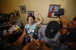 Opposition member María Adilia Peralta Cerratos raises her fist in defiance as she talks to the press during her return home after being in prison, in Masaya, Nicaragua, Monday, May 20, 2019. Peralta Cerratos is one of 100 prisoners the Nicaraguan government released Monday in a form of house arrest, including three human rights activists. (AP Photo/Alfredo Zuniga)
