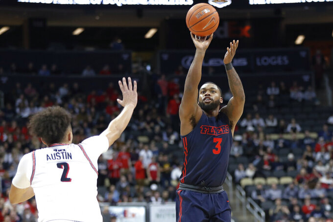 Dayton's Trey Landers (3) shoots as Duquesne's Maceo Austin (2) defends during the first half of an NCAA college basketball game Wednesday, Jan. 29, 2020, in Pittsburgh. (AP Photo/Keith Srakocic)