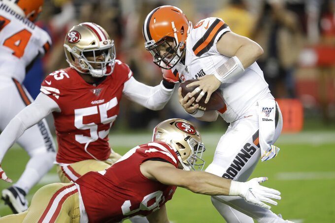Cleveland Browns quarterback Baker Mayfield, top right, is sacked by San Francisco 49ers defensive end Nick Bosa, bottom, during the first half of an NFL football game in Santa Clara, Calif., Monday, Oct. 7, 2019. Also pictured is 49ers defensive end Dee Ford (55). (AP Photo/Ben Margot)