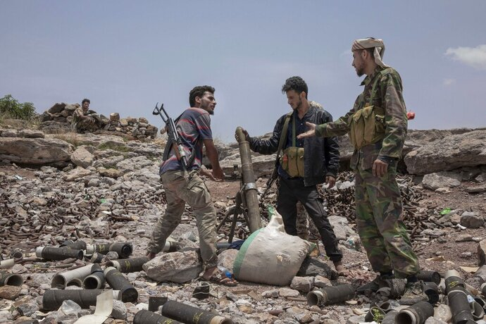 FILE - In this Monday, Aug. 5, 2019, file photo, fighters from a militia known as the Security Belt, that is funded and armed by the United Arab Emirates, discuss launching a mortar towards Houthi rebels, in an area called Moreys, on the frontline in Yemen's Dhale province. Saudi Arabia and the United Arab Emirates pledged Monday, Aug. 26, 2019, to keep their floundering coalition war against Yemen's Houthi rebels together after an Emirati troop pullout and the rise of the southern separatists they supported. (AP Photo/Nariman El-Mofty, File)