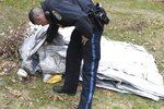 In this Sunday, Dec. 1, 2019, photo provided by Kevin Brown, a police officer inspects an evacuation slide that fell from a jetliner into the yard of a home in Milton, Mass. A Delta Air Lines spokeswoman said the uninflated slide fell from a flight from Paris to Boston midday as it approached for a landing. (Kevin Brown via AP)