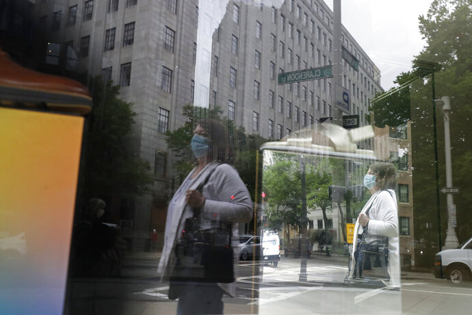 """FILE - In this June 11, 2020, file a passer-by wears a mask out of concern for the coronavirus while walking past a storefront window in Boston. Eighty-five percent of Democrats call economic conditions """"poor,"""" while 65% of Republicans describe them as """"good,"""" according to a new survey by The Associated Press-NORC Center for Public Affairs Research. (AP Photo/Steven Senne, File)"""