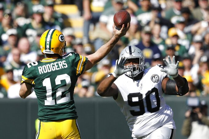 Green Bay Packers' Aaron Rodgers throws a touchdown pass in front of Oakland Raiders' Johnathan Hankins during the first half of an NFL football game Sunday, Oct. 20, 2019, in Green Bay, Wis. (AP Photo/Jeffrey Phelps)