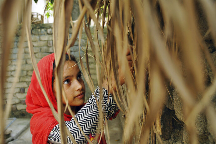 In this Tuesday, August 13, 2018, photo, Ansa Khan sifts through dry sugarcane peel and for use as firewood in Mardan, Pakistan. At just 10 years old, her day is a hectic one. At the first hint of dawn, she is up saying her morning prayers before reading her Quran, Islam's holy book. Those are Ansa's quietest moments. After that her day is a whirl of chores, school, studying and the occasional moments stolen away to play marbles. (AP Photo/Saba Rehman)