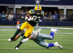 Green Bay Packers running back Aaron Jones (33) avoids a tackle attempt by Dallas Cowboys' Leighton Vander Esch during the second half of an NFL football game in Arlington, Texas, Sunday, Oct. 6, 2019. (AP Photo/Michael Ainsworth)