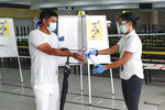 A voter, left, wearing a face mask, has his hand sanitized by a polling official after casting his vote at a polling station at the Chung Cheng High School polling center in Singapore, Friday, July 10, 2020. Wearing masks and plastic gloves, Singaporeans began voting in a general election that is expected to return Prime Minister Lee Hsien Loong's long-governing party to power. (AP Photo)