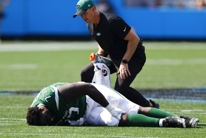 New York Jets offensive tackle Mekhi Becton is helped on the field during the second half of an NFL football game against the Carolina Panthers Sunday, Sept. 12, 2021, in Charlotte, N.C. (AP Photo/Nell Redmond)