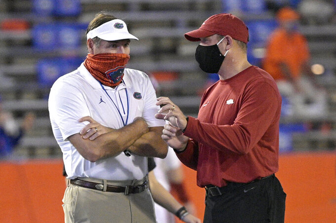 Florida head coach Dan Mullen, left, and acting Arkansas head coach Barry Odom talk on the field during warmups before an NCAA college football game, Saturday, Nov. 14, 2020, in Gainesville, Fla. (AP Photo/Phelan M. Ebenhack)