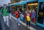 Students wear face masks as they leave a subway in Frankfurt, Germany, Wednesday, Oct. 28, 2020. (AP Photo/Michael Probst)