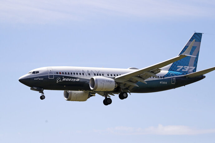 FILE - In this June 29, 2020, file photo, a Boeing 737 Max jet heads to a landing at Boeing Field following a test flight in Seattle. Aviation regulators and pilots from several countries will begin next week reviewing Boeing's proposal for training pilots to fly the revamped 737 Max, a sign that the grounded plane is moving closer to returning to service. The Federal Aviation Administration said Friday, Sept. 11, 2020, that the review will start Monday at London's Gatwick Airport and last about nine days. (AP Photo/Elaine Thompson, File)