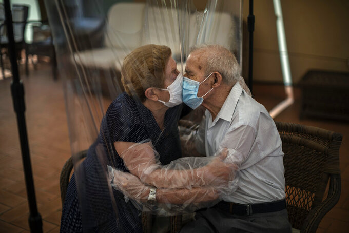 "Agustina Canamero, 81, and Pascual Pérez, 84, hug and kiss through a plastic film screen to avoid contracting the new coronavirus at a nursing home in Barcelona, Spain, June 22, 2020. Associated Press photographer Emilio Morenatti says this of the image: ""I couldn't help feeling emotional myself while I was shooting, and I realized that such an eternal moment symbolized something more than a simple meeting. The plastic kept the virus but not the love away."" (AP Photo/Emilio Morenatti)"