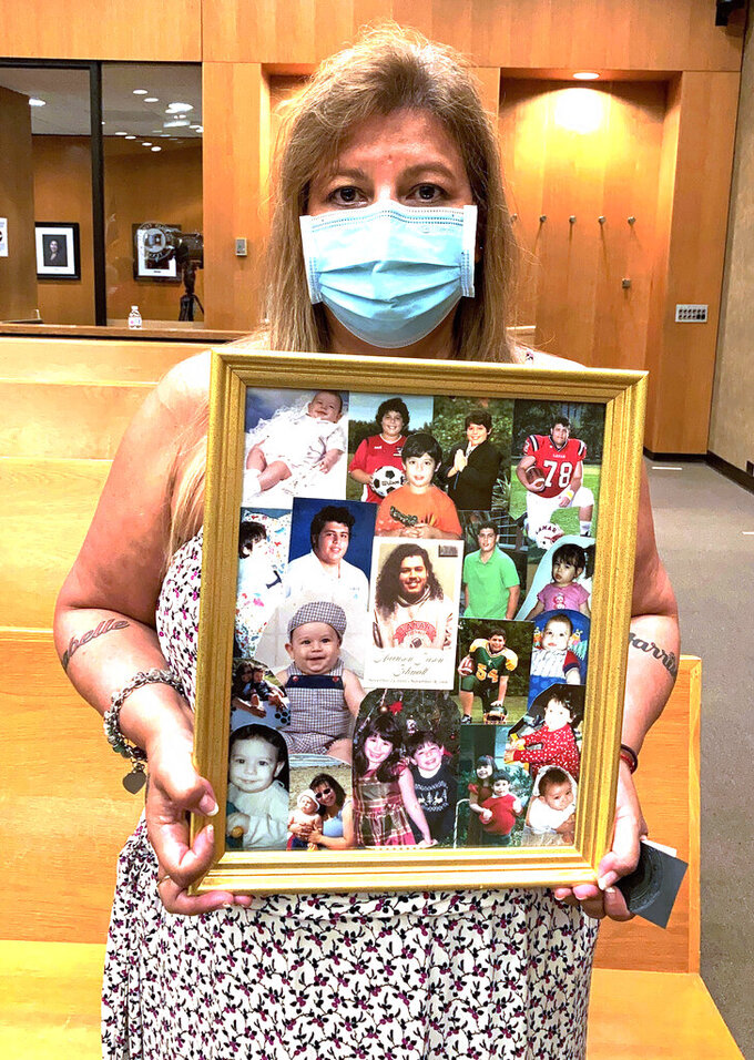Angelica Halphen, whose 18-year-old son Harrison Schmidt was killed in a 2019 road rage shooting in Houston, Texas holds photos of her son in Houston, Wednesday Sept. 1, 2021. Texas' new law allowing most people to carry handguns in public without a license or training came in part from the belief by many here that the best way to prevent crime and stop an armed bad guy is to make sure an armed good guy is nearby. (AP Photo/Juan A. Lozano)