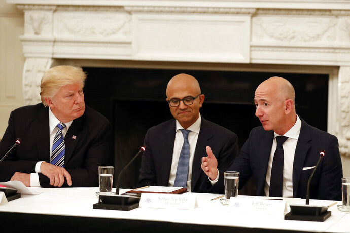 "FILE - In this June 19, 2017, file photo President Donald Trump, left, and Satya Nadella, Chief Executive Officer of Microsoft, center, listen as Jeff Bezos, Chief Executive Officer of Amazon, speaks during an American Technology Council roundtable in the State Dinning Room of the White House in Washington. Amazon and Microsoft are battling for a $10 billion opportunity to build the U.S. military its first ""war cloud."" (AP Photo/Alex Brandon, File)"
