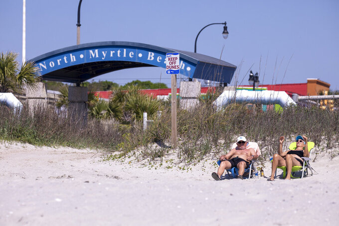Tommy and Marilyn Loudermilk enjoy the beach in North Myrtle Beach on Tuesday. Governor Henry McMaster removed his close order, allowing local municipalities to make their own decisions as of noon on Tuesday. North Myrtle Beach, S.C. April 20, 2020.  (Jason Lee/The Sun News via AP)