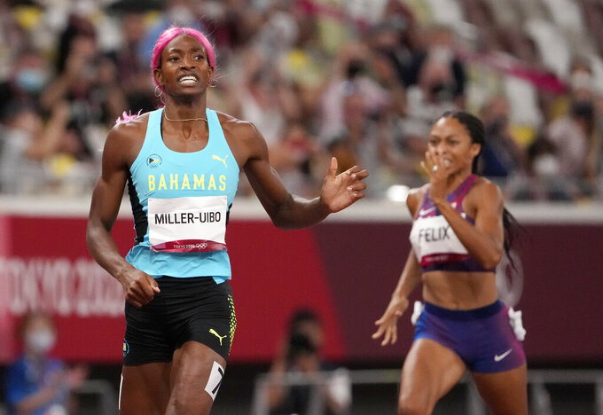 Shaunae Miller-Uibo, of Bahamas crosses the line to win the gold medal ahead of Allyson Felix, of United States, bronze, in the final of women's 400-meters at the 2020 Summer Olympics, Friday, Aug. 6, 2021, in Tokyo, Japan. (AP Photo/Charlie Riedel)