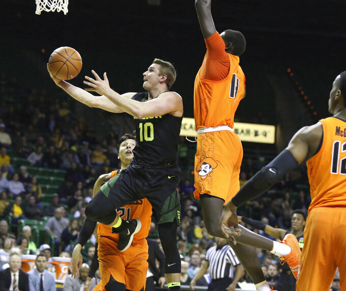 Baylor guard Makai Mason, left, drives and scores past Oklahoma State forward Yor Anei, center right, during the second half of an NCAA college basketball game Wednesday, March 6, 2019, in Waco, Texas. (Rod Aydelotte/Waco Tribune Herald via AP)
