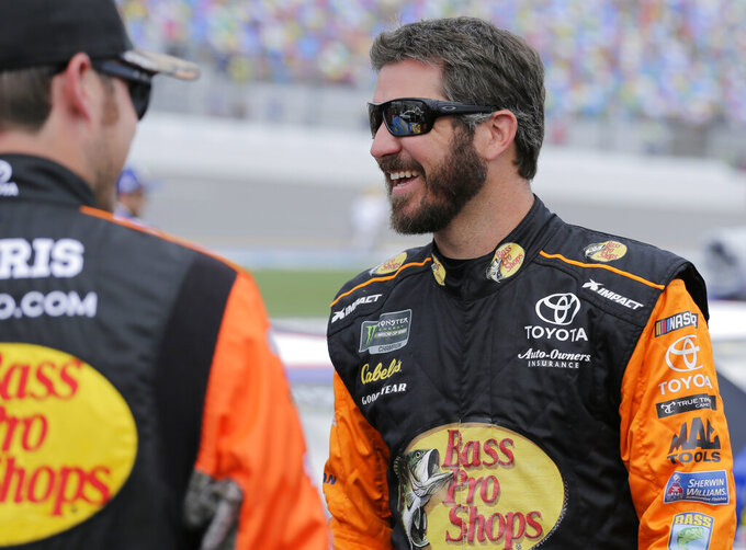 Martin Truex Jr. laughs with a crew member on pit road before a NASCAR auto race at Daytona International Speedway on Sunday, July 7, 2019, in Daytona Beach, Fla. (AP Photo/Terry Renna)