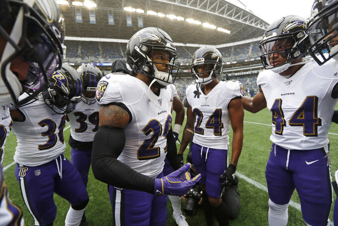 Baltimore Ravens free safety Earl Thomas (29) center, talks to teammates, including cornerbacks Marcus Peters (24) and Marlon Humphrey (44), in a huddle before an NFL football game against the Seattle Seahawks, Sunday, Oct. 20, 2019, in Seattle. (AP Photo/Elaine Thompson)