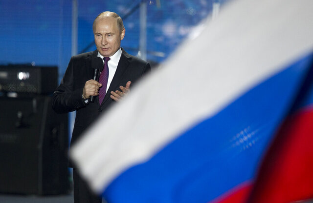 FILE - In this file photo dated Wednesday, March 14, 2018, Russian President Vladimir Putin speaks in front of a Russian National flag in Sevastopol, Crimea.  An influential committee of British lawmakers plans to publish its findings Tuesday July 21, 2020, reporting on Russian interference in British politics, amid criticism the government delayed its release for more than six months to shield Prime Minister Boris Johnson and his Conservative Party from embarrassment. (AP Photo/Alexander Zemlianichenko, FILE)