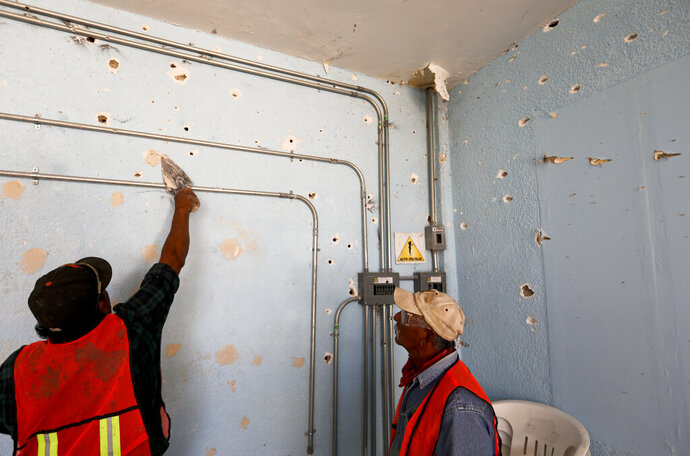 A worker repairs a wall riddled with bullet holes at City Hall in Villa Union, Mexico, Monday, Dec. 2, 2019. The small town near the U.S.-Mexico border began cleaning up Monday even as fear persisted after 22 people were killed in a weekend gun battle between a heavily armed drug cartel assault group and security forces. (AP Photo/Eduardo Verdugo)