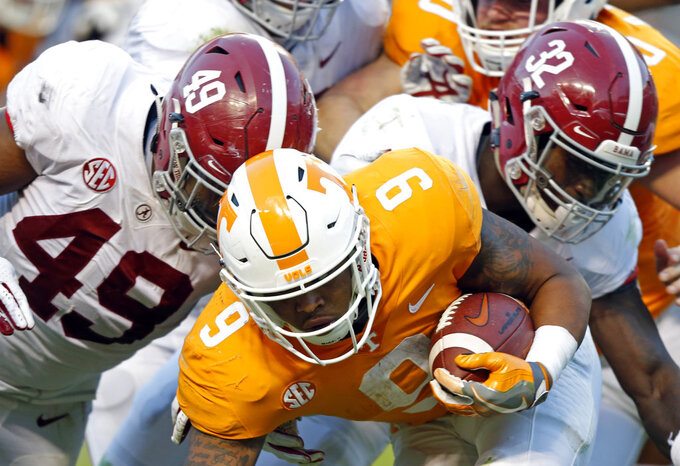 Tennessee running back Tim Jordan (9) is tackled by Alabama defensive lineman Isaiah Buggs (49) and linebacker Dylan Moses (32) during the second half of an NCAA college football game Saturday, Oct. 20, 2018, in Knoxville, Tenn. Alabama won 58-21. (AP Photo/Wade Payne)