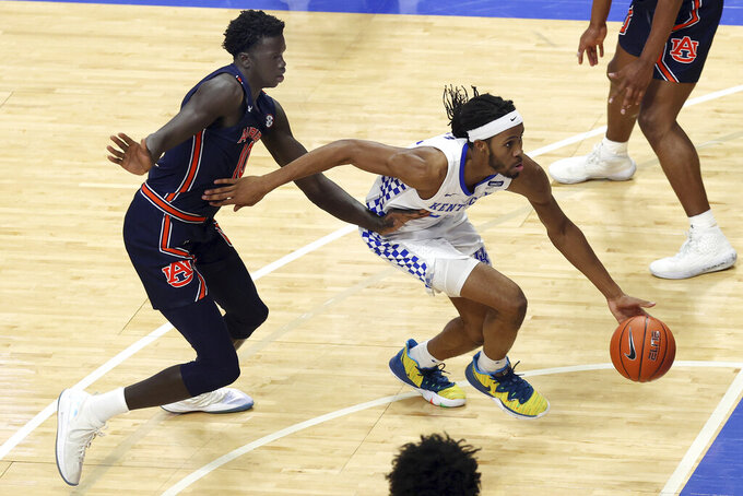 Kentucky's Isaiah Jackson, right, drives in front of Auburn's JT Thor during the second half of an NCAA college basketball game in Lexington, Ky., Saturday, Feb. 13, 2021. (AP Photo/James Crisp)