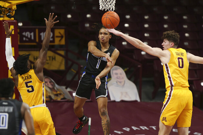 Saint Louis's Yuri Collins (1) passes the ball through the defense of Minnesota's Marcus Carr (5) and Minnesota's Liam Robbins (0) during an NCAA college basketball game Sunday, Dec. 20, 2020, in Minneapolis. (AP Photo/Stacy Bengs)
