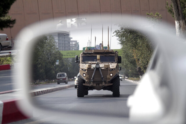 FILE - In this Aug. 23, 2017, file photo, a patrolling U.S. armored vehicle is reflected in the mirror of a car in Kabul, Afghanistan. An accelerated U.S. troop withdrawal from Afghanistan, announced by Washington, Tuesday, Nov. 17, 2020, has rattled both allies and adversaries and raised fears of worsening violence and regional chaos, which some say could embolden the Islamic State affiliate in the country to try to regroup in a lawless Afghanistan. (AP Photo/Rahmat Gul, File)