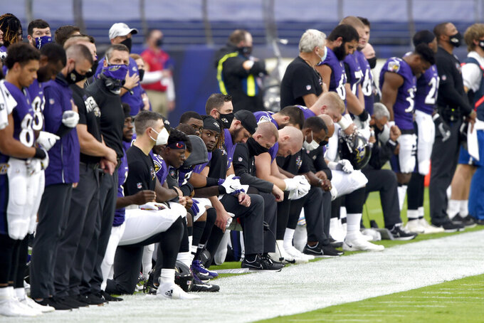 Baltimore Ravens players take a knee during the playing of the national anthem prior to an NFL football game against the Cincinnati Bengals, Sunday, Oct. 11, 2020, in Baltimore. (AP Photo/Gail Burton)