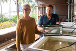 This photo taken  June 11, 2021, shows Margaret McFall-Ngai, lead scientist at the University of Hawaii's Kewalo Marine Laboratory, left, and lab manager Randall Scarborough standing with a squid in Honolulu. Dozens of baby squid from Hawaii are in space for study. The baby Hawaiian bobtail squid were raised at the Kewalo Marine Laboratory and were blasted into space earlier this month on a SpaceX resupply mission to the International Space Station. (Craig T. Kojima, Honolulu Star-Advertiser via AP)