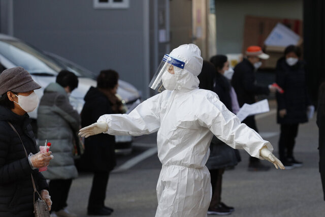 A medical worker wearing protective gear speaks as people wait in queue during testing for COVID-19 at a coronavirus testing center in Seoul, South Korea, Saturday, Dec. 12, 2020. (AP Photo/Lee Jin-man)