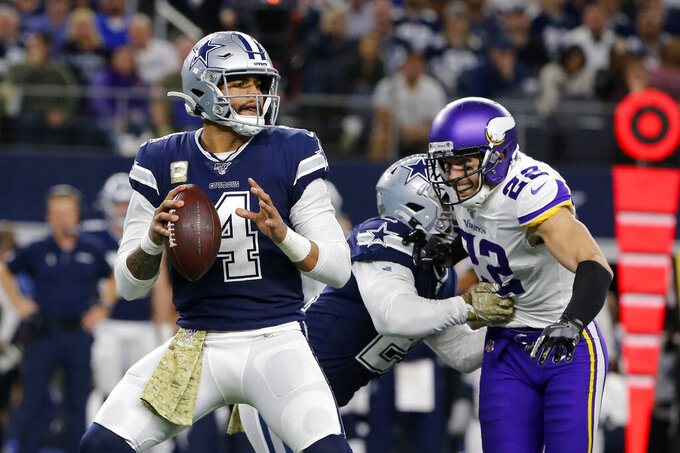Dallas Cowboys quarterback Dak Prescott (4) prepares to throw a pass as Minnesota Vikings' Harrison Smith (22) pressures him during the first half of an NFL football game in Arlington, Texas, Sunday, Nov. 10, 2019. (AP Photo/Michael Ainsworth)