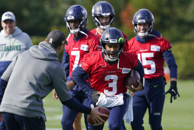 Seattle Seahawks quarterback Russell Wilson (3) keeps his injured hand in a pad as he runs through a warmup drill with backup quarterback Geno Smith (7) behind him during NFL football practice, Wednesday, Oct. 13, 2021, in Renton, Wash. Wilson had surgery on his hand last Friday, and Smith is expected to be the starting quarterback Sunday when the Seahawks play the Pittsburgh Steelers on the road. (AP Photo/Ted S. Warren)